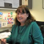 Photo of Marjorie Kruvand, sitting at their desk wearing green sweater